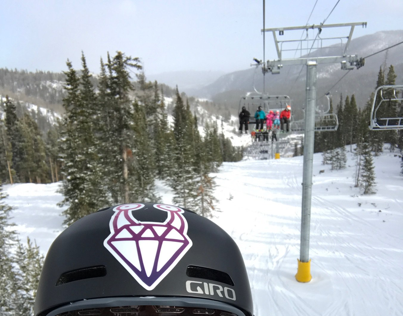 A Keep Ruby Weird sticker on a helmet in a snowy and woody area with a ski lift seat with five people behind