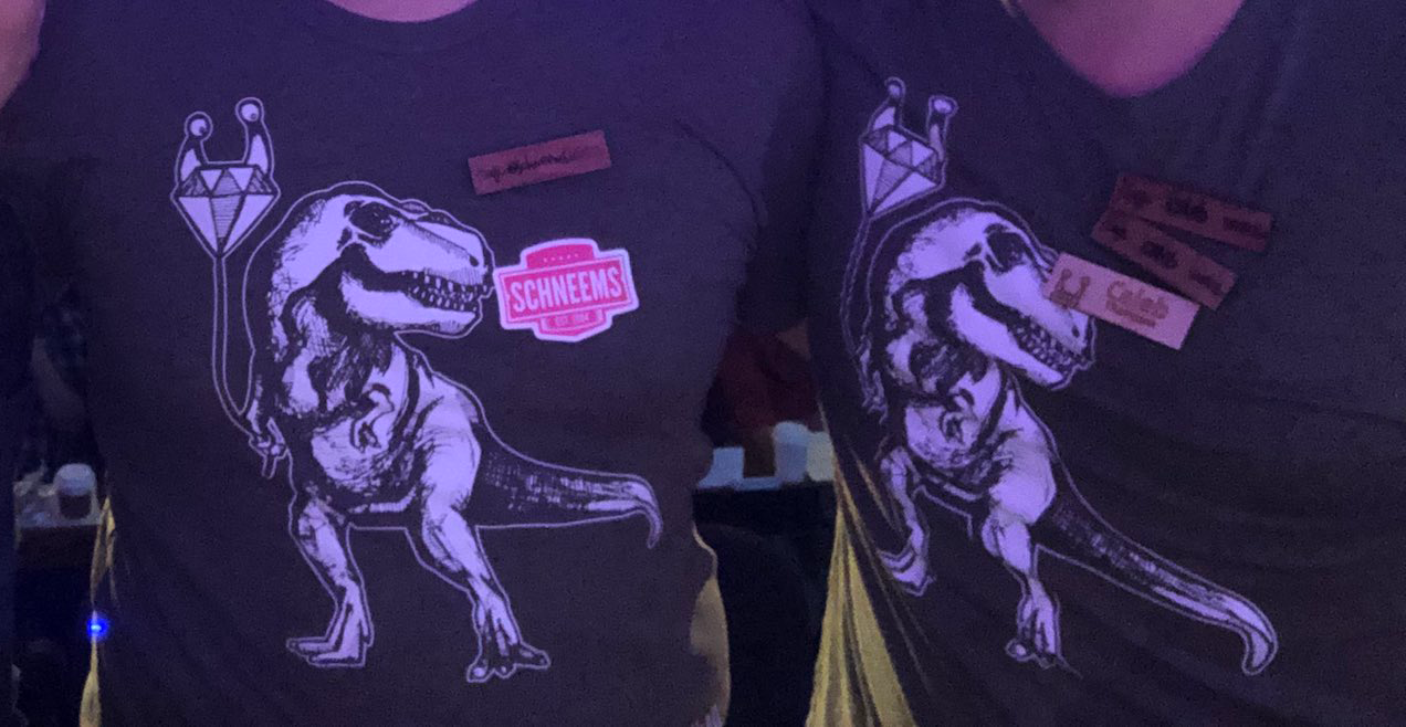 Two people wearing an olive shirt with a graphic of a T-rex holding a Keep Ruby Weird ballon
