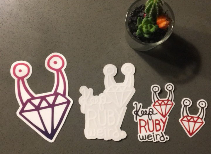 Four different Keep Ruby Weird stickers layed out on a table with a succulent