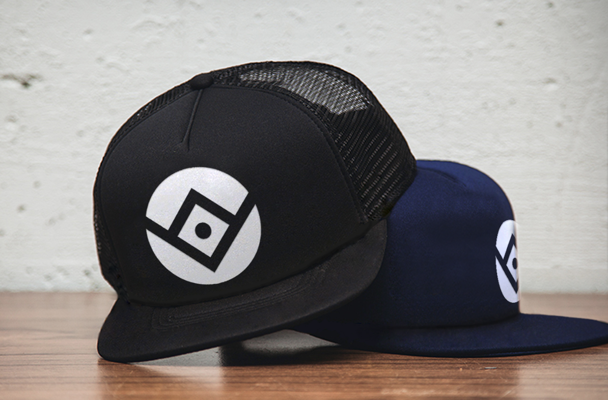 A black trucker hat and a blue hat with the Ottoneu logo mark on them